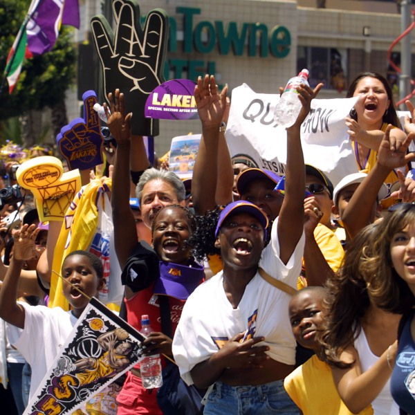 Los Angeles Lakers fans cheer as a float with team members aboard approaches during a parade through downtown Los Angeles, CA celebrating the team's third consecutive NBA championship 14 June, 2002. (LEE CELANO/AFP via Getty Images)