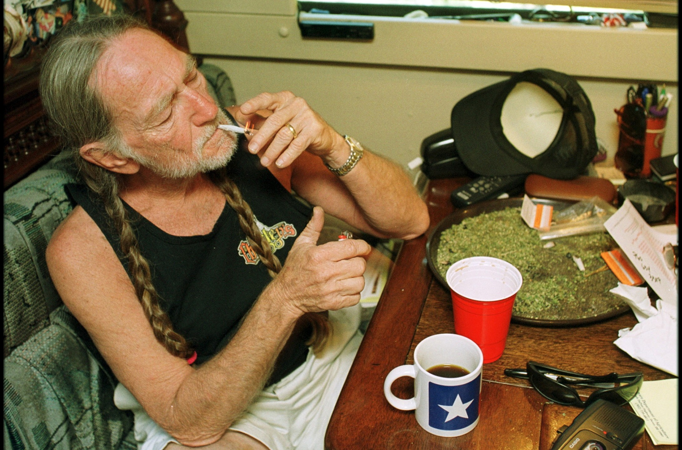 American country singer Willie Nelson takes a drag off a joint while relaxing at his home in Texas during the early 2000s. (Liaison/Getty Images)