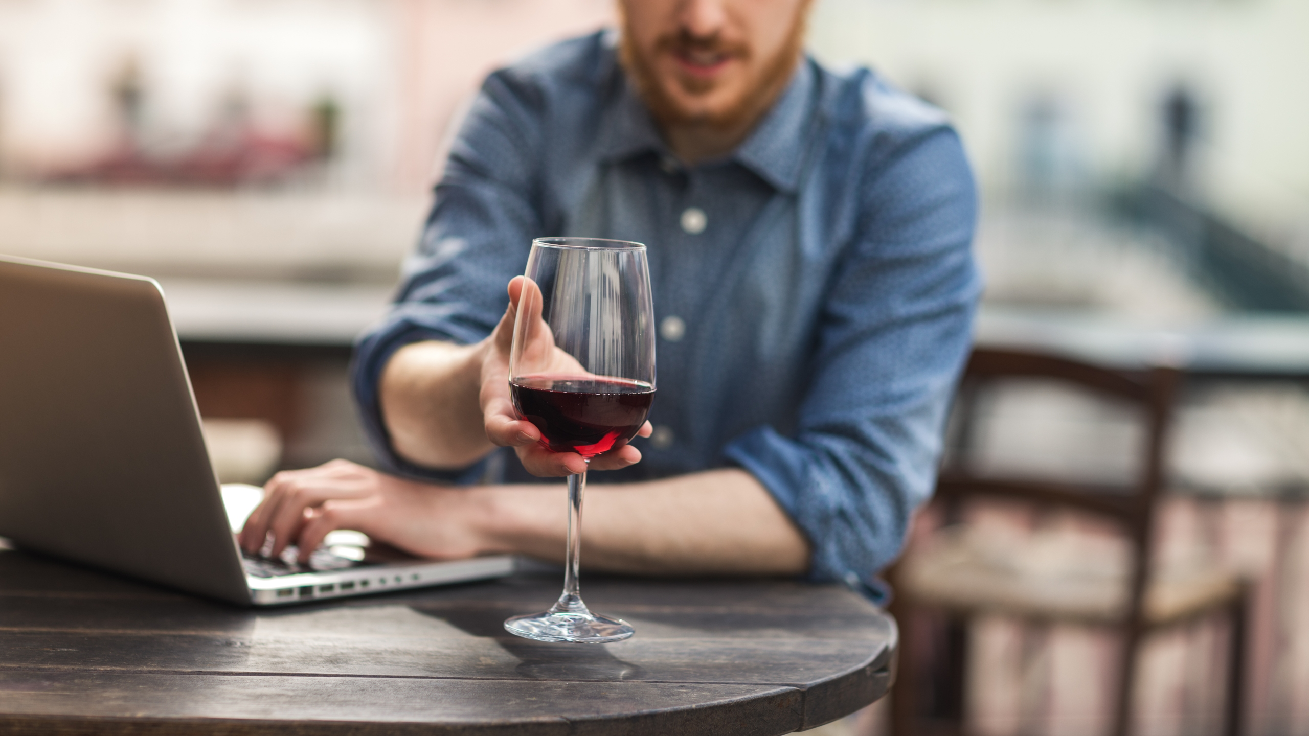 A man reaches for a glass of wine as he uses his laptop in this undated file photo. (Getty Images)