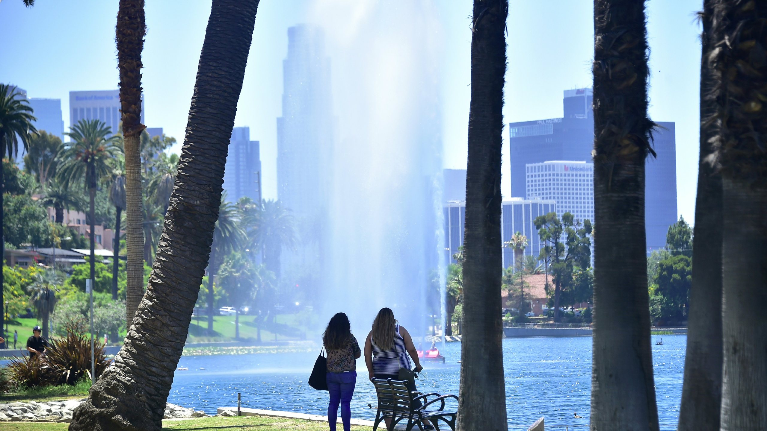 Women cool off with a view of a fountain and sprinkles of water blowing in the breeze at Echo Park lake on June 26, 2017. (FREDERIC J. BROWN/AFP via Getty Images)