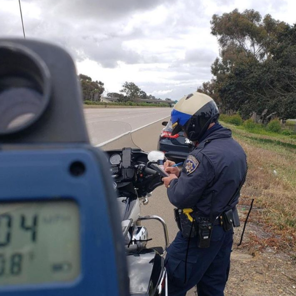 A California Highway Patrol officer issues a speeding citation on the 5 Freeway in San Diego County on April 15, 2020, in a photo released by CHP San Diego.