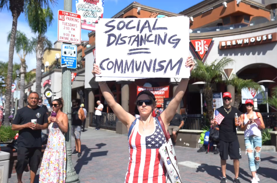 A demonstrator in Huntington Beach protests against local and statewide stay-at-home orders amid the coronavirus pandemic on April 17, 2020. (OC Hawk)
