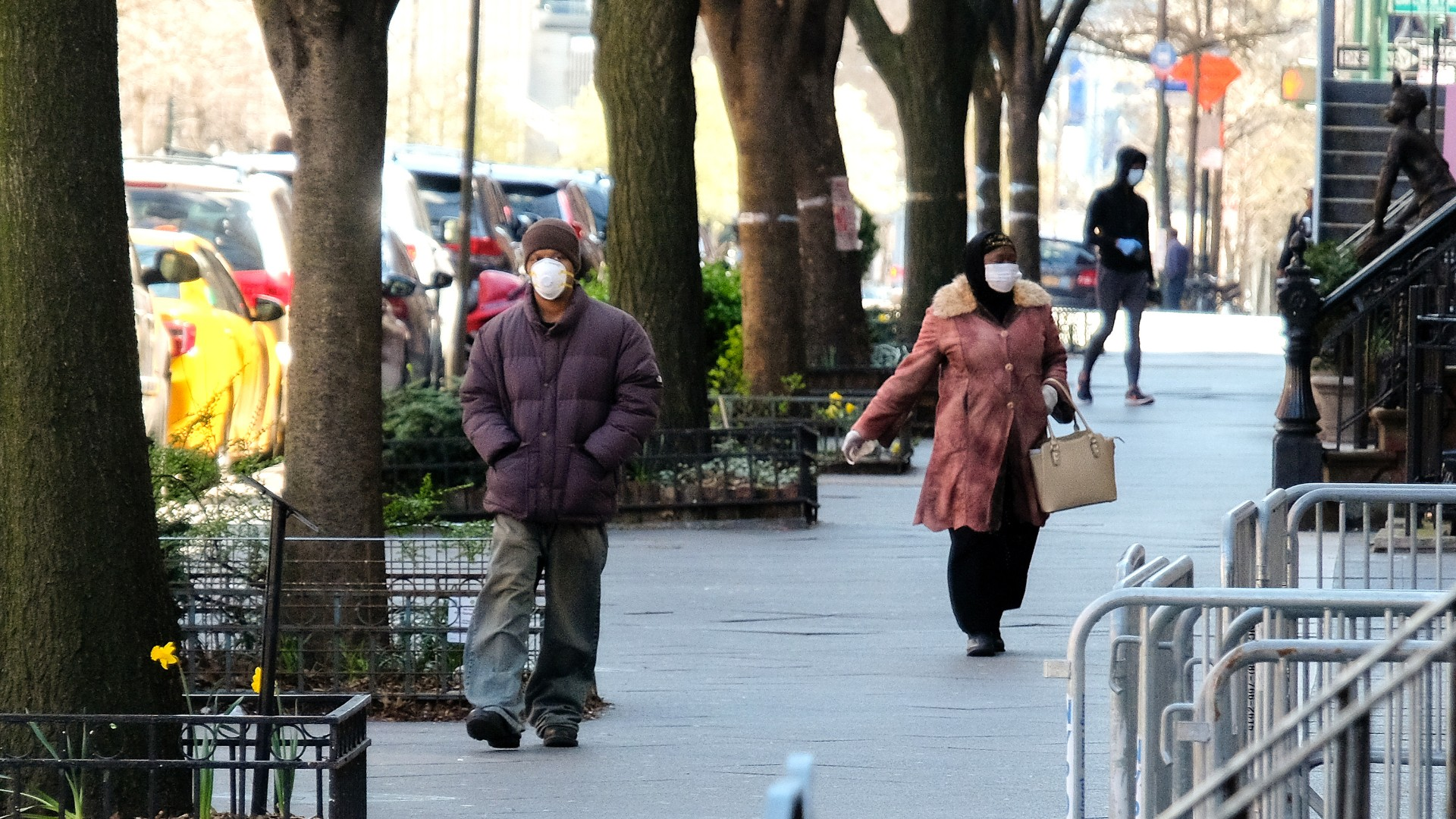People wearing protective masks are seen walking in the Harlem neighborhood of Manhattan as the coronavirus continues to spread across the United States on April 2, 2020 in New York City. (Dia Dipasupil/Getty Images)