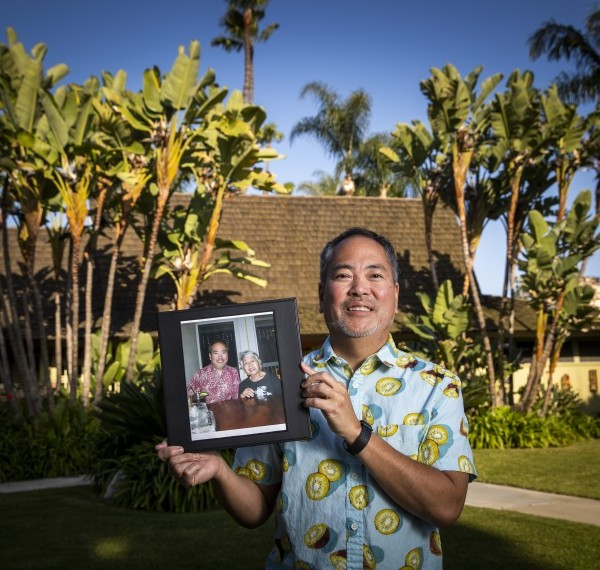 Mason Nakamura holds a photo of himself with his late mother, Mary Nakamura, at his home in Santa Ana. (Allen J. Schaben / Los Angeles Times)