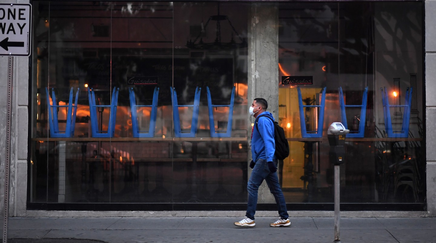 A man in a mask passes a closed restaurant along Spring Street in downtown Los Angeles. (Wally Skalij/Los Angeles Times)