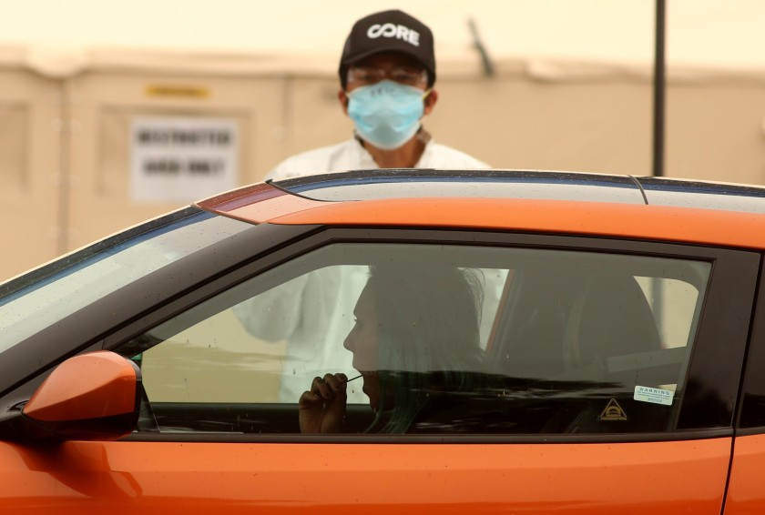 A woman takes a self-administered COVID-19 test, under the instruction of a health worker, at a drive-up testing site outside Jackie Robinson Stadium off the UCLA campus.(Genaro Molina / Los Angeles Times)