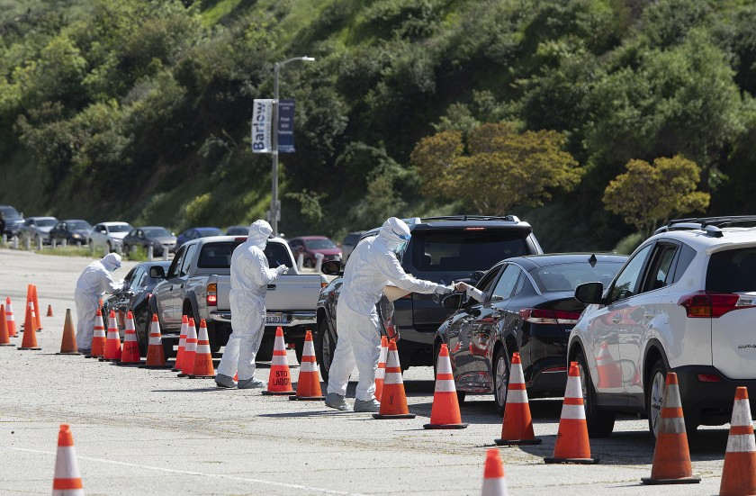 Members of the Los Angeles Fire Department wear protective gear as they hand out coronavirus test kits in a parking lot on Stadium Way, near Dodger Stadium. (Mel Melcon / Los Angeles Times)