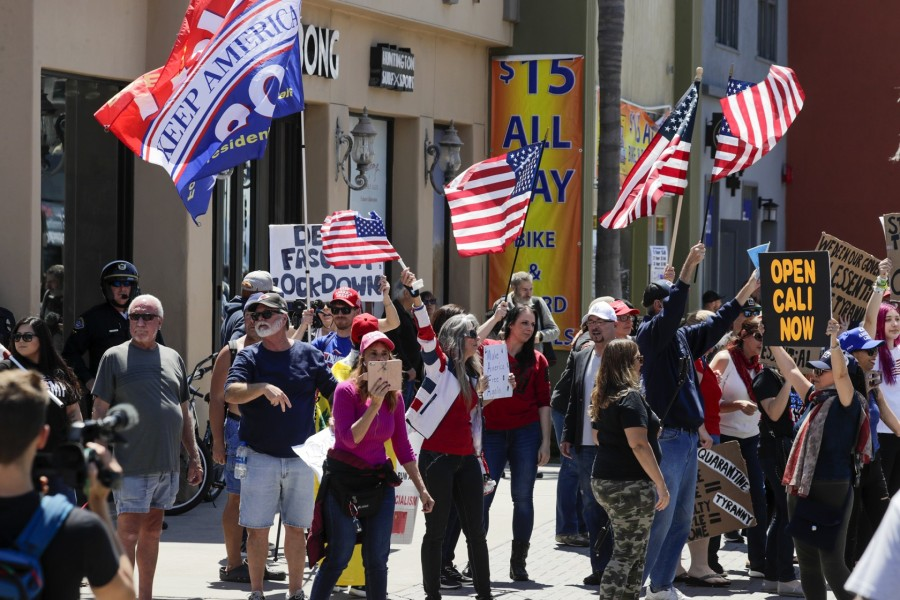 People pushing for the reopening of California businesses amid the coronavirus pandemic rally on Main Street in Huntington Beach on April 17, 2020. (Irfan Khan/Los Angeles Times)