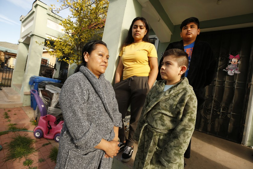 Raquel Lezama, left, outside her home in Los Angeles after walking with her daughter Monica Ramos, center, to Manual Arts High School to pick up grab-and-go meals for the family.(Al Seib/Los Angeles Times)