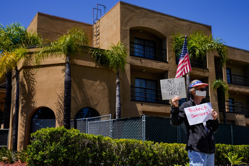 Protester Karen Litfin of Laguna Hills stands outside the Laguna Hills Inn, which the county is planning to use to house homeless people with the coronavirus, in this undated photo. (Credit: Kent Nishimura / Los Angeles Times)