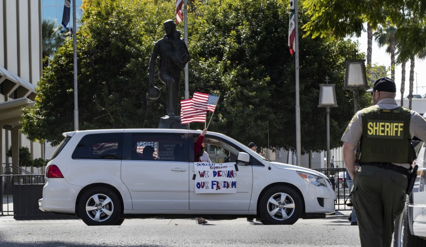A demonstrator waves an American flag at a Riverside County sheriff's deputy in 2020 while participating in a car rally to protest conditions in the county's jails, which has endured a coronavirus outbreak.(Gina Ferazzi / Los Angeles Times)