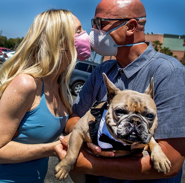 Tracey and Chad Robbins, with their dog, Huggy, kiss after their wedding ceremony at the Honda Center parking lot in Anaheim in April 2020. (Apu Gomes / AFP/Getty Images)