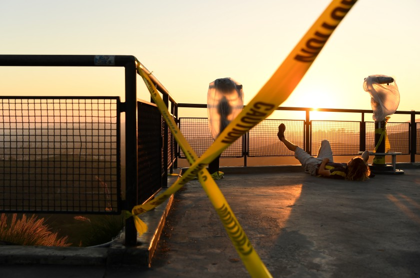 A man relaxes next to caution tape at Griffith Observatory as Los Angeles remains locked down because of the coronavirus on April 28, 2020. (Wally Skalij / Los Angeles Times)