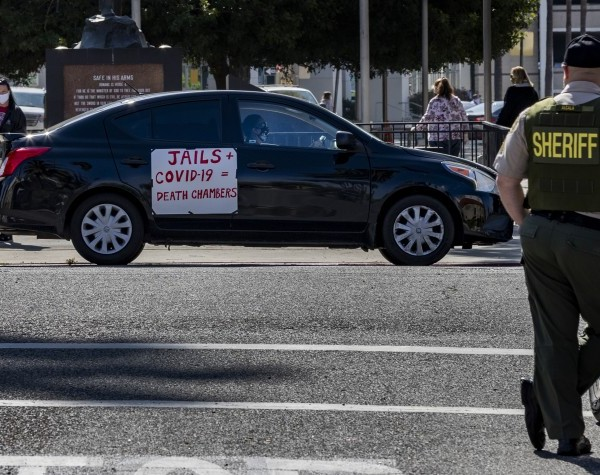 A Riverside County sheriff's deputy keeps watch during a car rally to protest conditions in Riverside County jails, where there has been a coronavirus outbreak. (Gina Ferazzi / Los Angeles Times)
