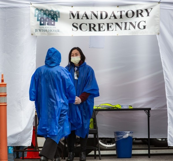 A worker at Eisenberg Village, an assisted living facility in Reseda conducts screenings for people with coronavirus symptoms in March 2020. (Jason Armond / Los Angeles Times)