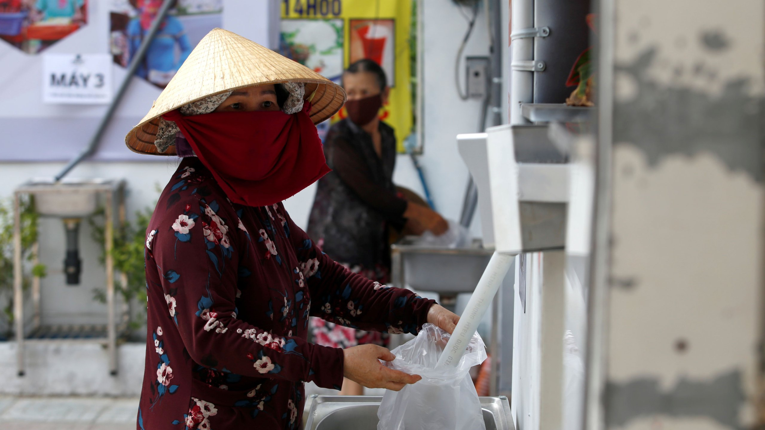 A woman fills a plastic bag with rice from a 24/7 automatic rice dispensing machine in Ho Chi Minh City, Vietnam, on April 11, 2020. (Yen Duong/Reuters)