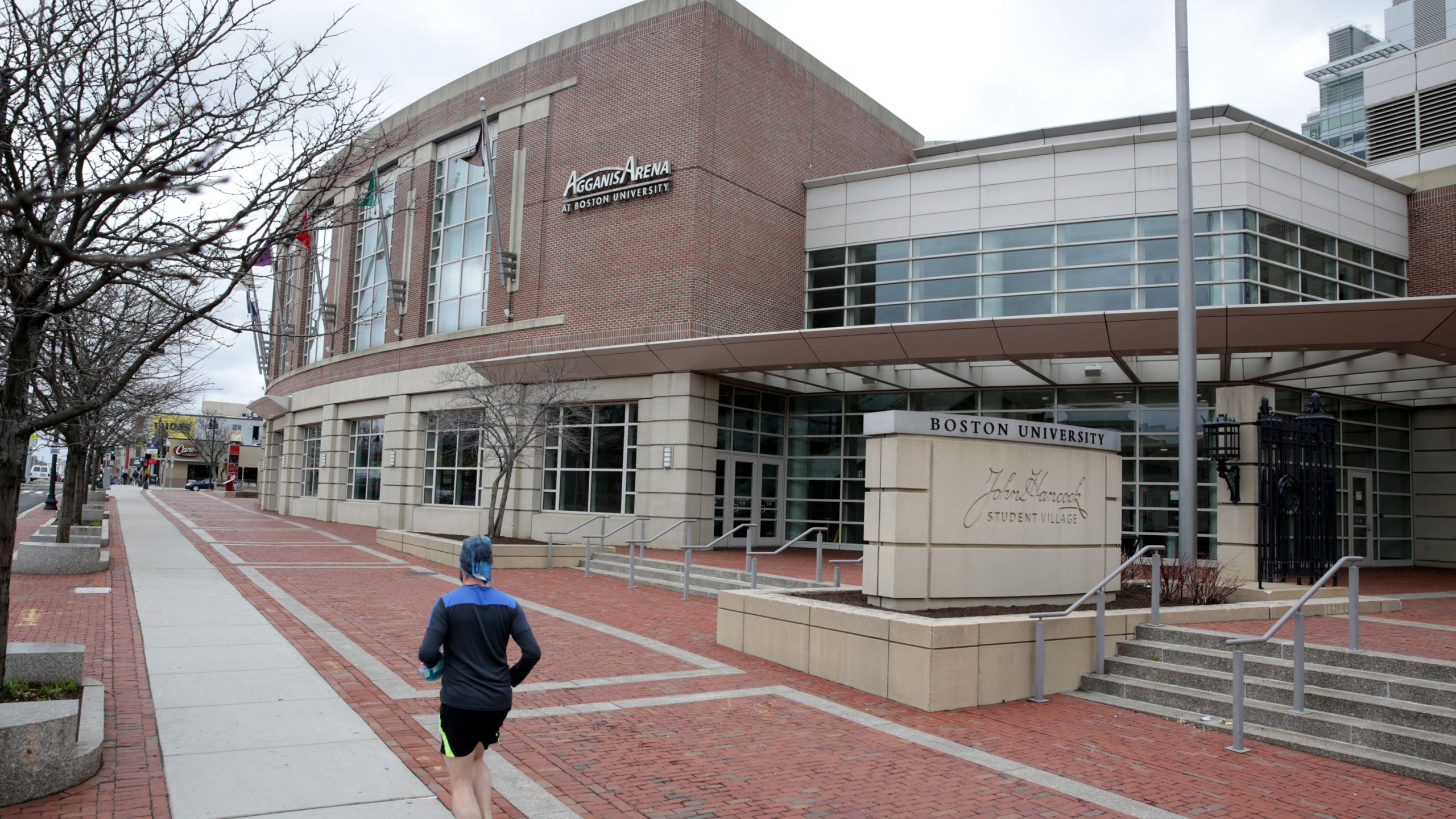 A person runs past Agganis Arena at Boston University along Commonwealth Ave. in Boston on March 25, 2020. Agganis Arena was set to host the Women's Frozen Four hockey tournament, but the event was cancelled. The coronavirus pandemic has postponed, suspended or cancelled many major sporting events and seasons. (Jonathan Wiggs/The Boston Globe via Getty Images)