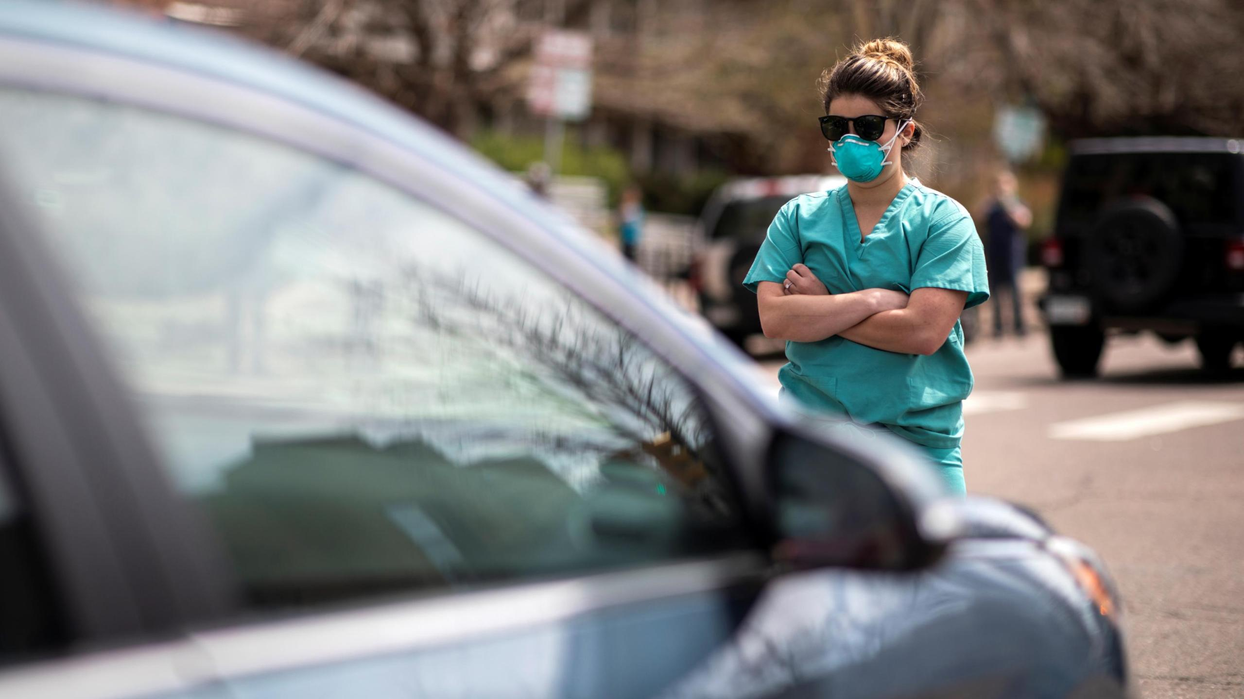A health care worker stands in the street in counterprotest to the hundreds of people demanding the stay-at-home order be lifted in Denver, Colorado on April 19, 2020. (Alyson McClaran/Reuters)