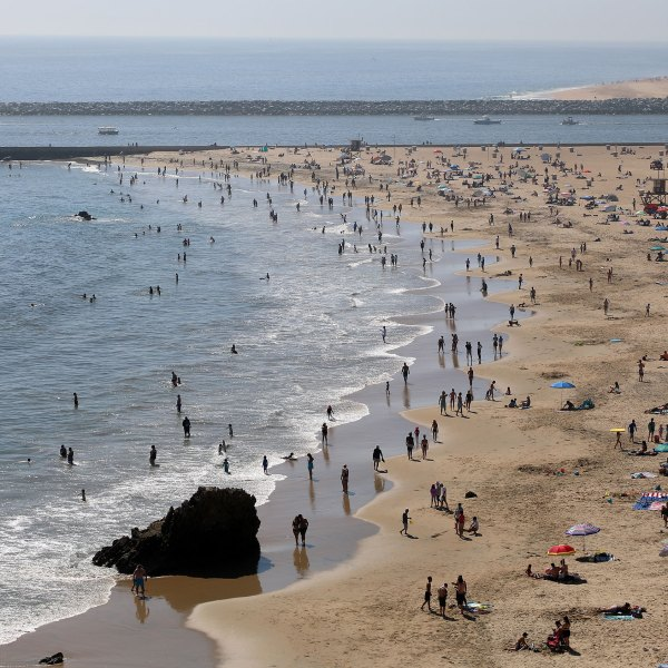 People are seen gathering on the Corona del Mar State Beach on April 25, 2020 in Newport Beach. (Michael Heiman/Getty Images)