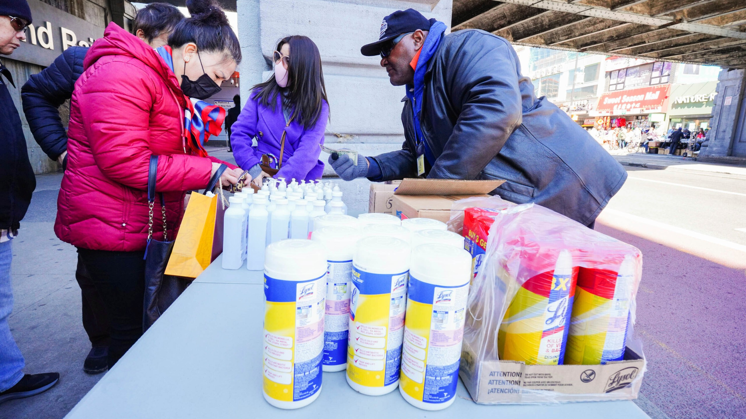 People wear protective masks to fend off the Coronavirus, while street vendors pedal masks, hand sanitizer and other disinfecting products in Queens, New York. (John Nacion/STAR MAX/IPx/AP)