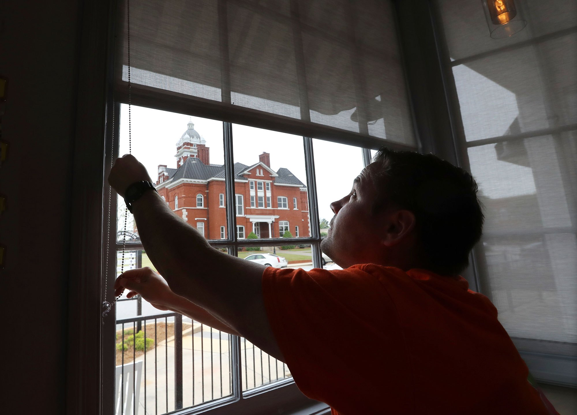 Brian Lambert, owner of a coffee and sweets shop in Forsyth, Georgia, opens the windows of his business as he gets ready to reopen next week. (Curtis Compton/AP via CNN Wire)