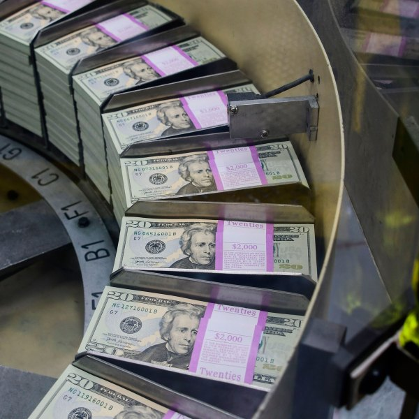 Packs of freshly printed 20 USD notes are processed for bundling and packaging at the US Treasury's Bureau of Engraving and Printing in Washington, DC July 20, 2018. (EVA HAMBACH/AFP via Getty Images)