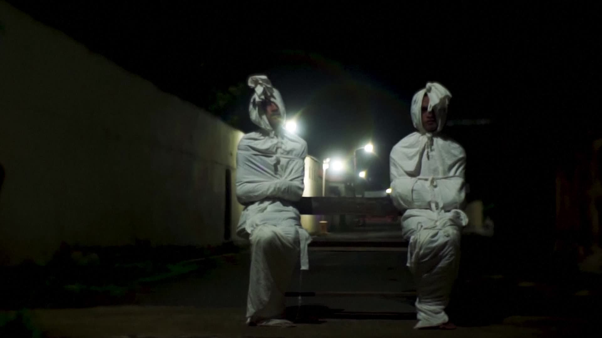 """Deri Setyawan, 25, and Septian Febriyanto, 26, dress up as """"pocong"""" ghosts in an attempt to make people in Kepuh village, in Indonesia's central Java province, stay at home during the coronavirus outbreak. (Reuters)"""