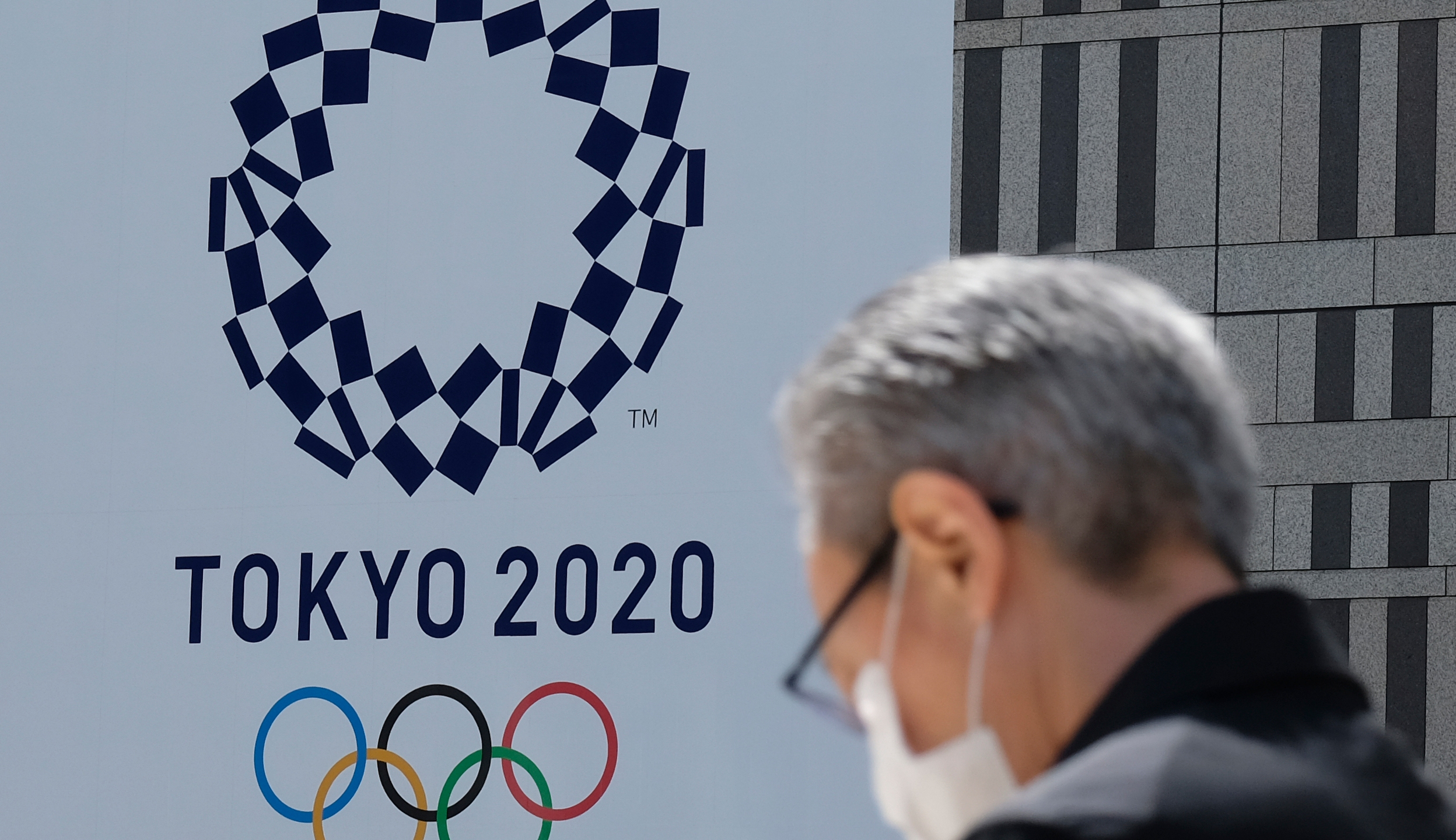 A man wearing a face mask walks before the logo of the Tokyo 2020 Olympic Games displayed on the Tokyo Metropolitan Government building in Tokyo on March 24, 2020. - The International Olympic Committee came under pressure to speed up its decision about postponing the Tokyo Games on March 24 as athletes criticised the four-week deadline and the United States joined calls to delay the competition. (Photo by Kazuhiro NOGI / AFP) (Photo by KAZUHIRO NOGI/AFP via Getty Images)