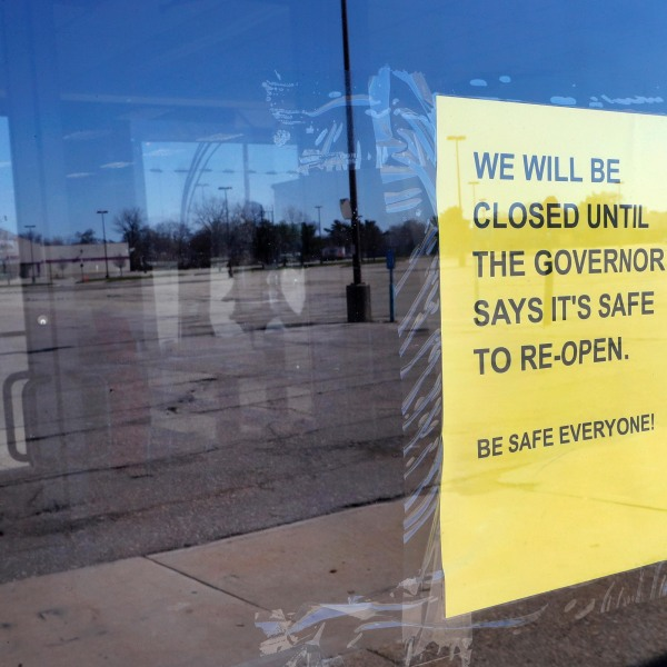 A closed sign is shown with an empty parking lot in Detroit, Thursday, April 2, 2020. (Paul Sancya/AP)