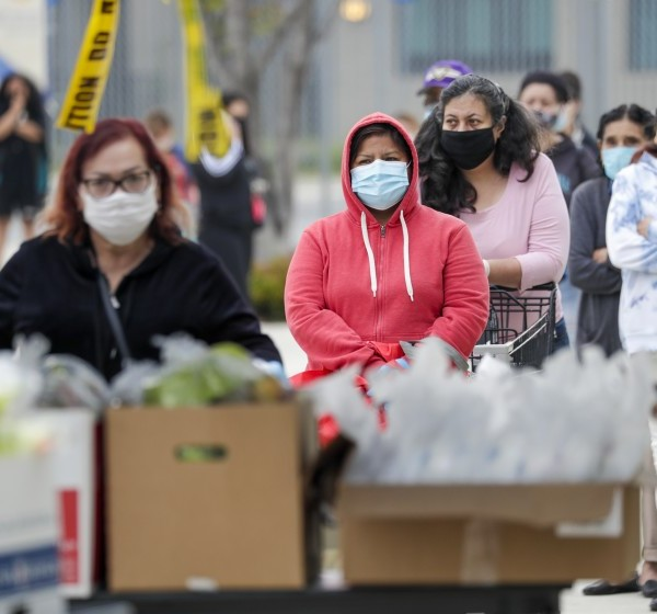 """People wait in line Friday to get meal packs provided by the Los Angeles Unified School District at the """"grab-and-go"""" food center in front of Byrd Middle School in Sun Valley, part of the district's exploding costs related to the COVID-19 pandemic.(Irfan Khan / Los Angeles Times)"""