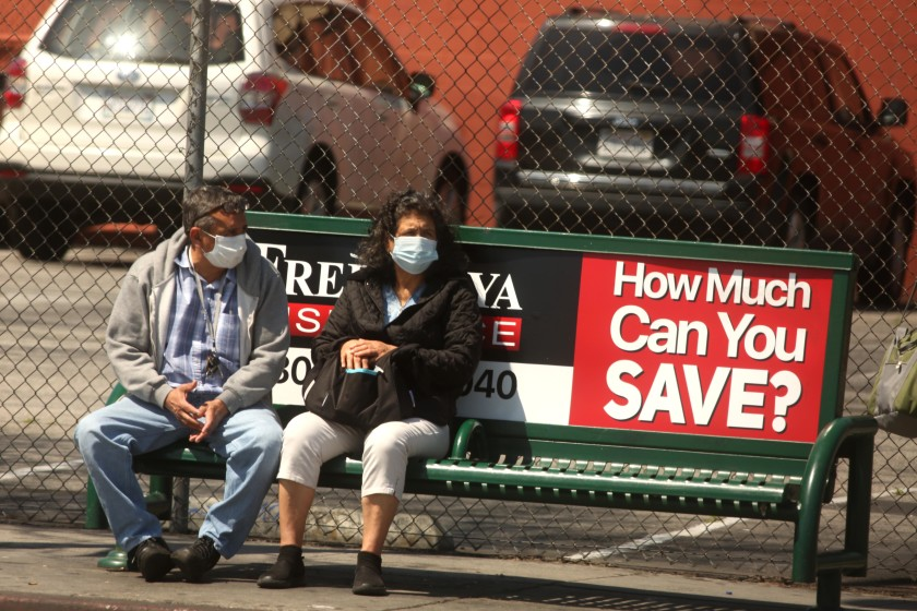 A man and a woman wear masks while waiting for a bus in Los Angeles in this undated photo. (Genaro Molina / Los Angeles Times)
