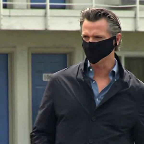 Gov. Gavin Newsom walks outside a Santa Clara County motel set to shelter homeless people amid the coronavirus pandemic ahead of a briefing on April 18, 2020. (CNN)