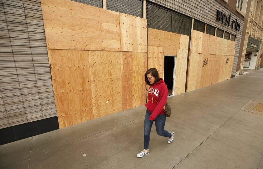 Elena Girotto walks past the boarded-up West Elm store on Colorado Boulevard in Pasadena on April 2, 2020. (Al Seib/Los Angeles Times)