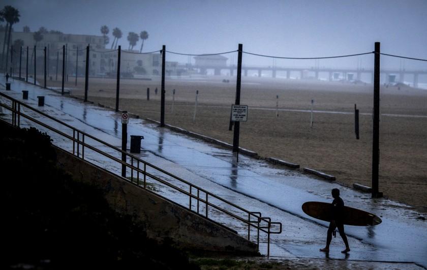 A surfer walks on an empty bike path amid steady rainfall in Huntington Beach in April 2020. (Allen J. Schaben / Los Angeles Times)