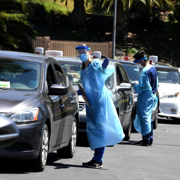 Workers wearing personal protective equipment perform drive-up COVID-19 testing administered from a car at Mend Urgent Care testing site for the novel coronavirus at the Westfield Culver City on April 24, 2020. (Kevin Winter/Getty Images)