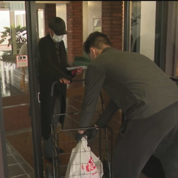 Jacon Kraus, 16, of Culver City, founder of covidconnections.com, delivers groceries to a senior citizen on April 10, 2020. (KTLA)