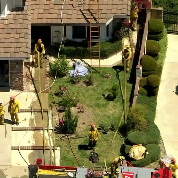 Firefighters mop up the scene of a blaze at a two-story home in Walnut on April 16, 2020. (KTLA)