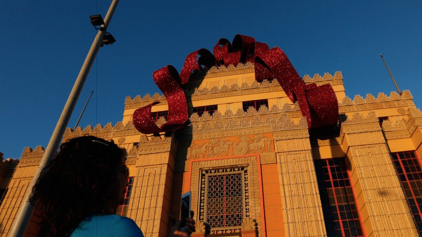 A visitor snaps a photo beneath the Citadel Outlets' holiday bow in an undated photo. (Gary Coronado / Los Angeles Times)