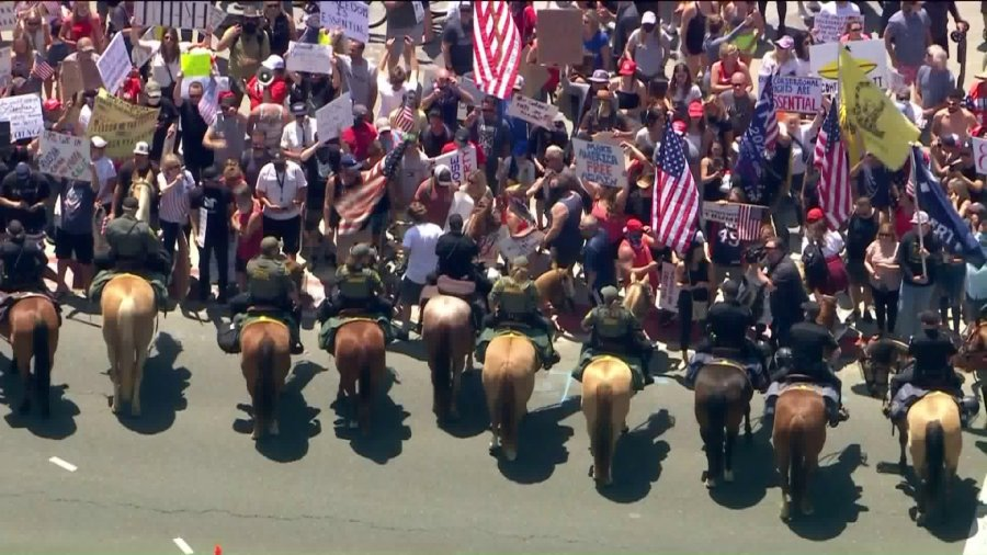 Law enforcement officials in Huntington Beach could be seen herding protestors out of the street during a protest against stay-at-home orders on May 1, 2020.