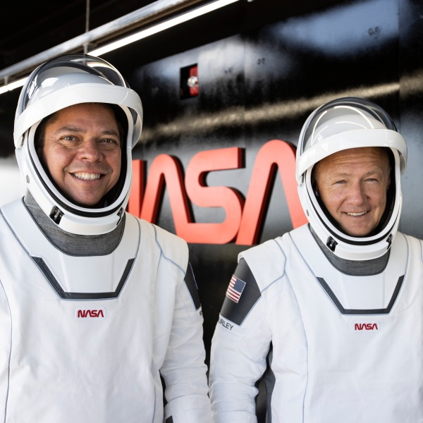 Two men wearing spacesuits pose in front of a sign for NASA on Jan. 3, 2020. (SpaceX/Flickr)