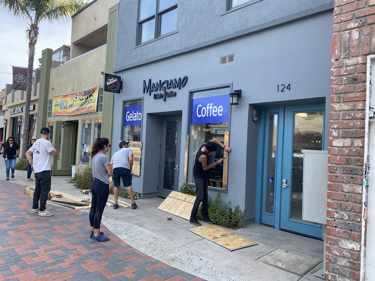 People board up businesses in Huntington Beach as hundreds gather for protests against the killing of George Floyd. (@MarcPeeblesPIO/ Twitter)