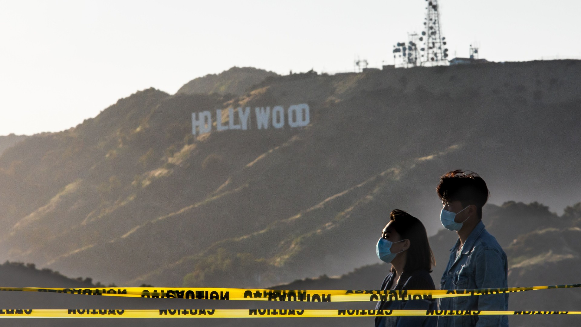 People wearing facemasks walk at the Griffith Observatory with a view of the Hollywood sign at the start of Memorial Day holiday weekend amid the novel coronavirus pandemic in Los Angeles on May 22, 2020. (Apu Gomes/Getty Images)