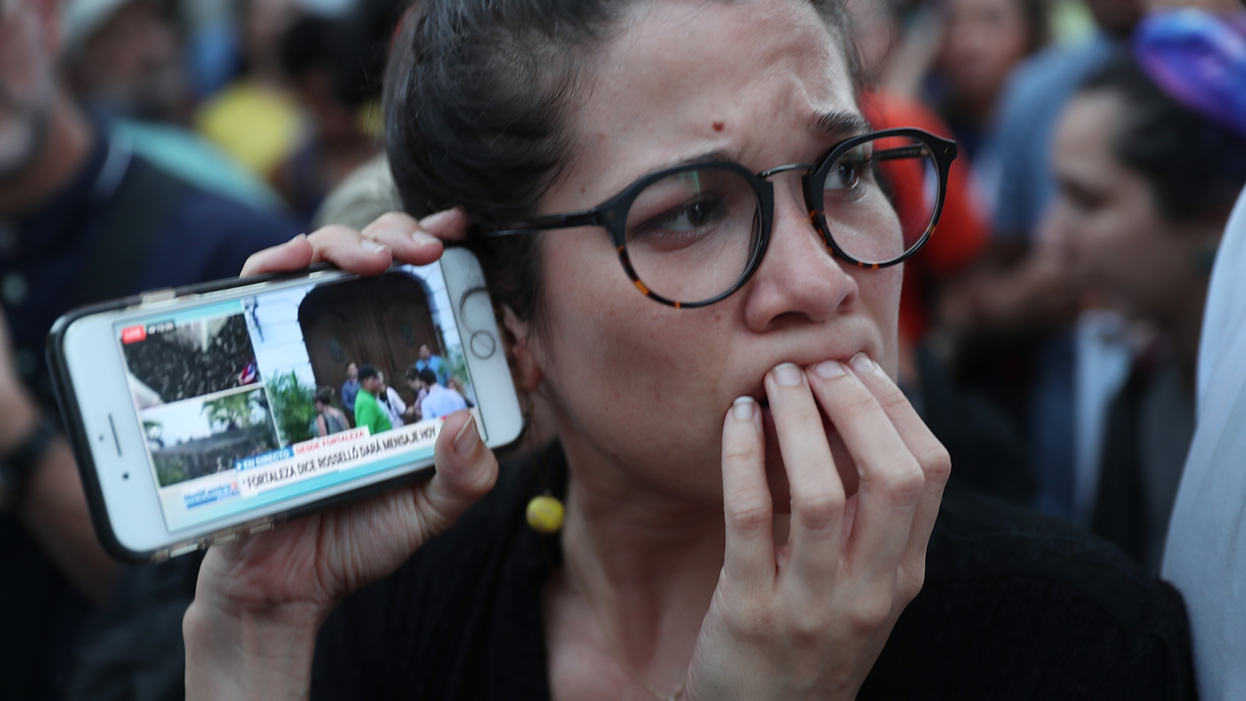 Protesters listen to a broadcast from inside the governor's mansion on their mobile phones as expectations remained high that Gov. Ricardo Rosselló would step down on July 24, 2019 in Old San Juan, Puerto Rico. (Joe Raedle/Getty Images)