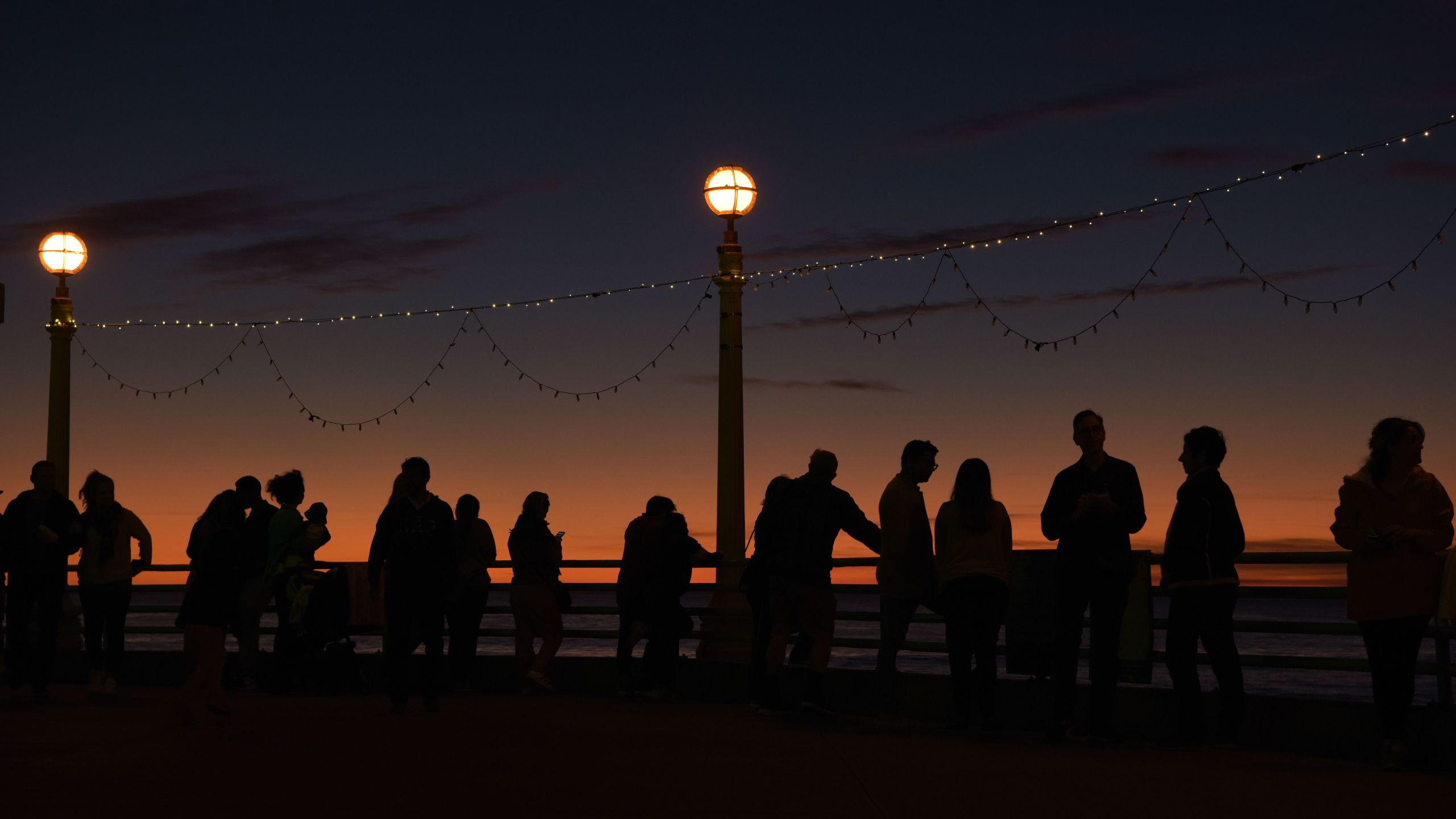 People enjoy the last sunset of the year on the pier in Manhattan Beach on Dec. 31, 2019. (Credit: Agustin Paullier / AFP / Getty Images)