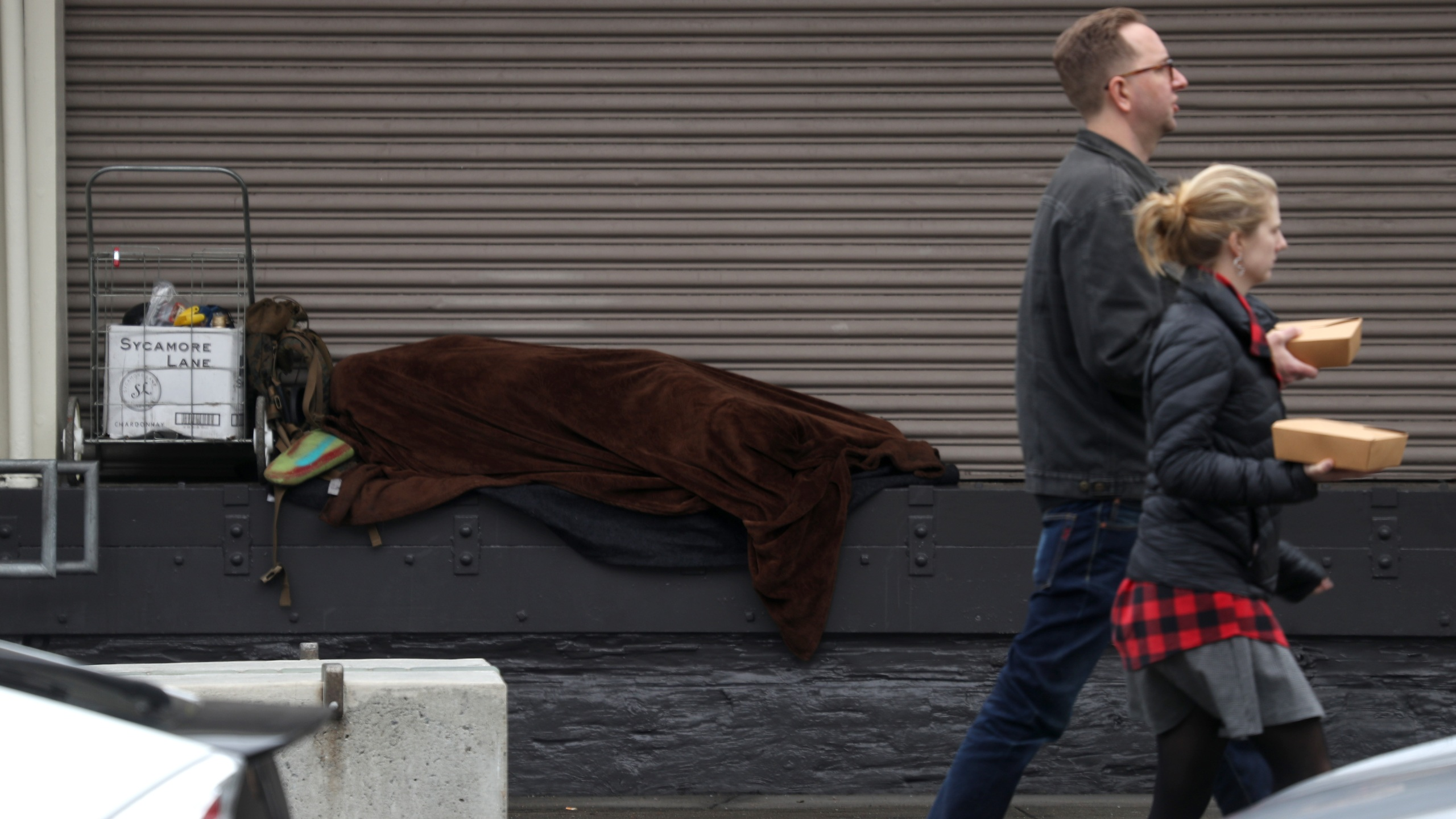 A homeless person sleeps on a loading dock in San Francisco on Dec. 5, 2019. (Credit: Justin Sullivan / Getty Images)