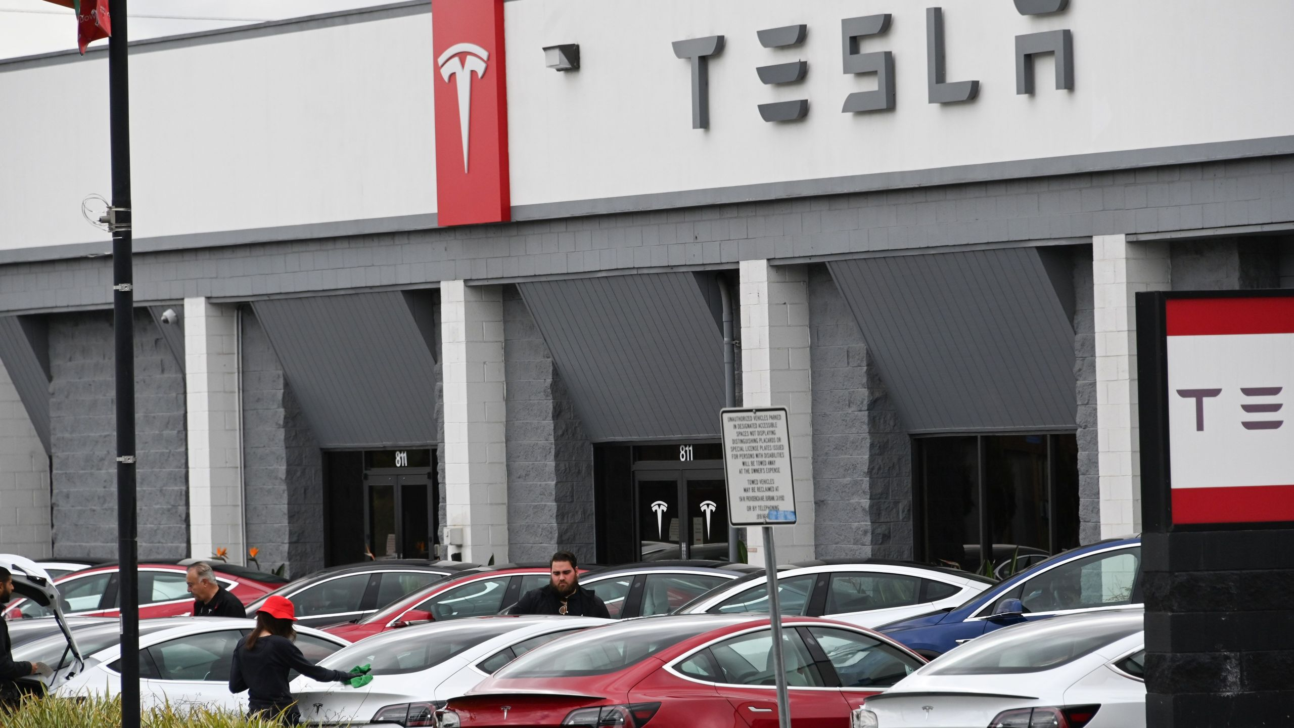 Tesla employees work outside a Tesla showroom in Burbank on March 24, 2020. (Credit: Robyn Beck / AFP / Getty Images)