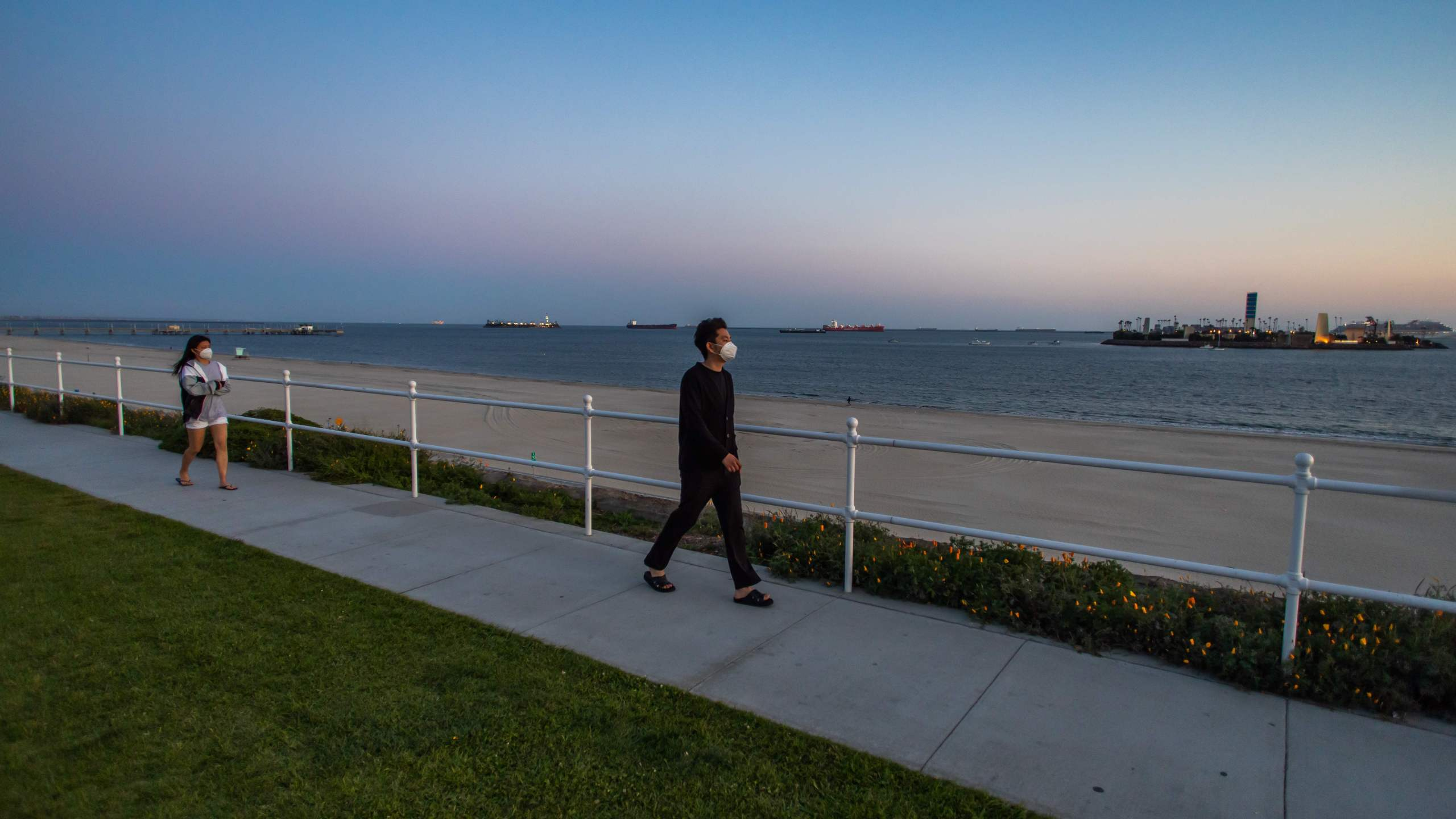 People walk by the sea in Long Beach, California on March 29, 2020. (APU GOMES/AFP via Getty Images)