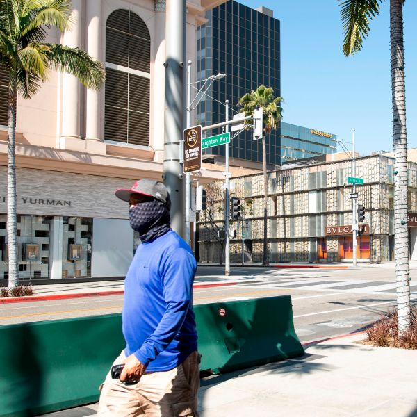 A person wearing a mask walks on Rodeo Drive in Beverly Hills on April 1, 2020, during the Covid 19 crisis. (VALERIE MACON/AFP via Getty Images)