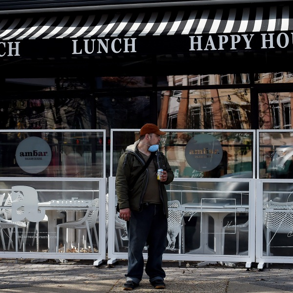 A man wearing a face mask stands outside a closed restaurant as local bussiness try to adapt due to concerns with the spread of the coronavirus on April 2, 2020 in Arlington, Virg. (OLIVIER DOULIERY/AFP via Getty Images)