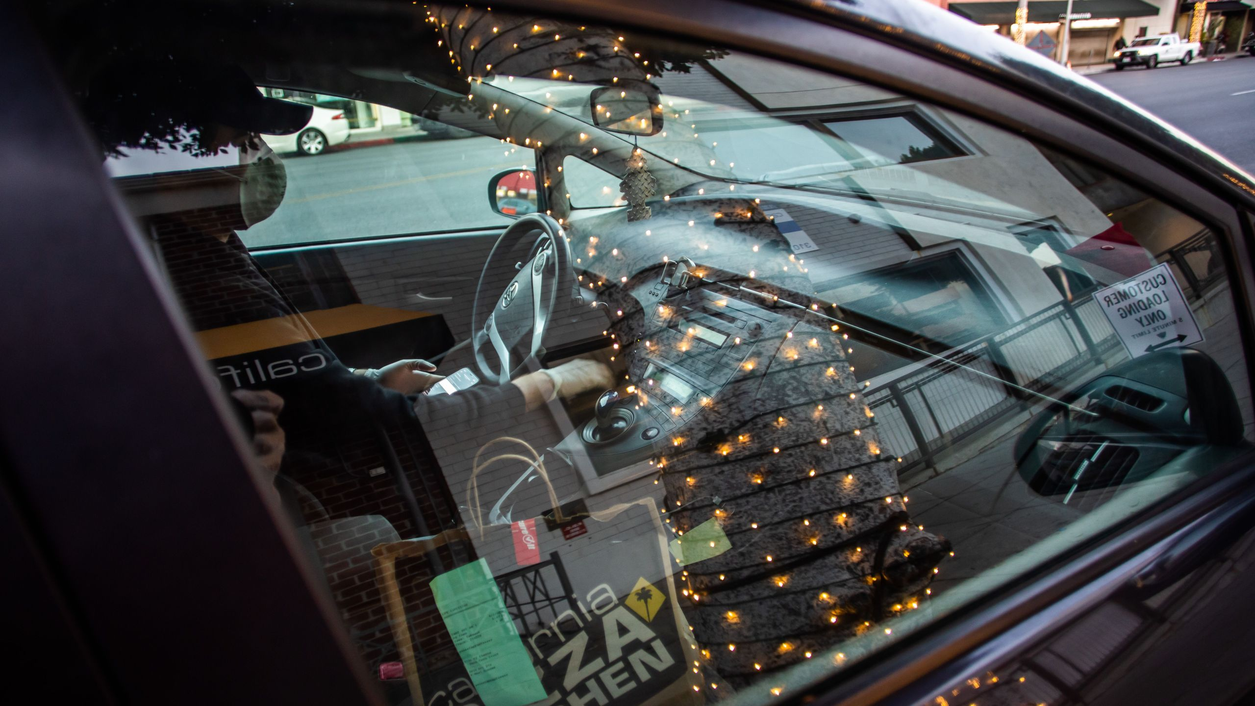 Musician Lucas Goes wears a mask as he drives to deliver food for a delivery app in Beverly Hills on April 2, 2020, after losing his job during the coronavirus outbreak. (Apu Gomes / AFP / Getty Images)